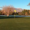 A view of a green with water coming into play and mountains in background at El Rio Golf Course.
